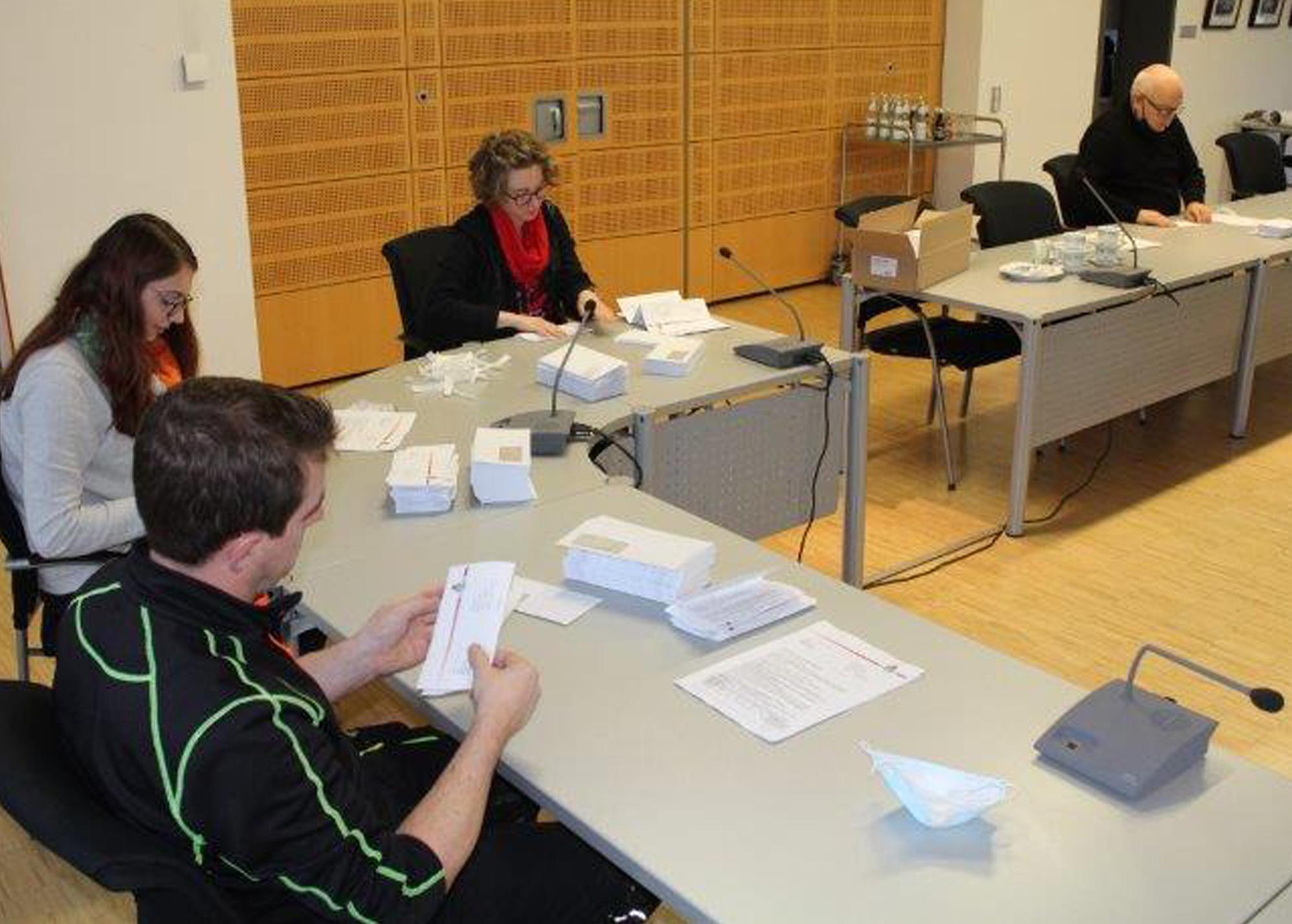 Mitarbeiter und Ehrenamtliche beim Vorbereiten der Informationsbriefe. Bürgermeister Kunkel (re) legt selbst mit Hand an.